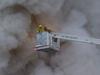 Firefighters in a lift with smoke behind them